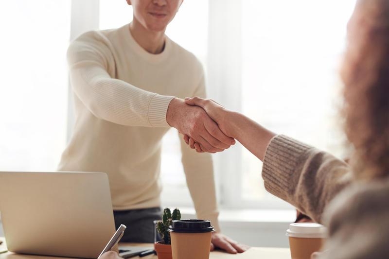 Doi oameni strângând mâna după un interviu.